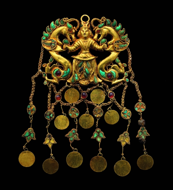 """Pendant showing the """"dragon master"""". Found in the tomb of a nomad woman in her 30s or 40s. Gold, turqoise, garnet, carnelian and pearl. 2nd quarter of 1st century AD. Souce: Thierry Ollivier / National Geographic."""